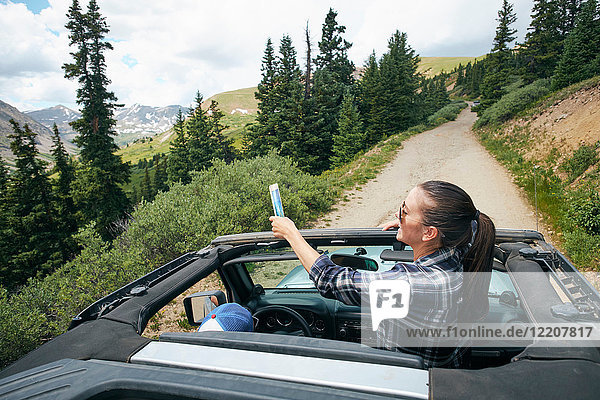 Young woman on road trip taking smartphone selfie travelling in convertible  Breckenridge  Colorado  USA