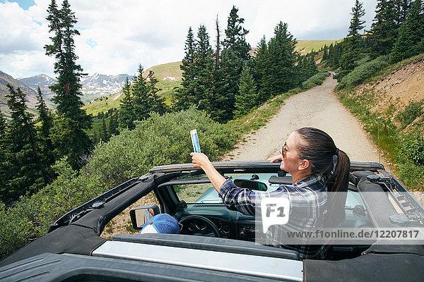 Junge Frau auf Autoreise mit Smartphone-Selfie im Cabrio  Breckenridge  Colorado  USA
