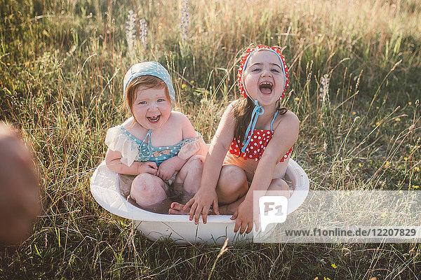 Zwei Mädchen auf dem Feld  die in einer Plastikwanne mit Wasser spielen