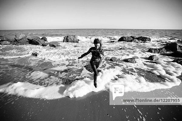 Frau rennt am Strand vor der Meereswelle davon  Oblast Odessa  Ukraine
