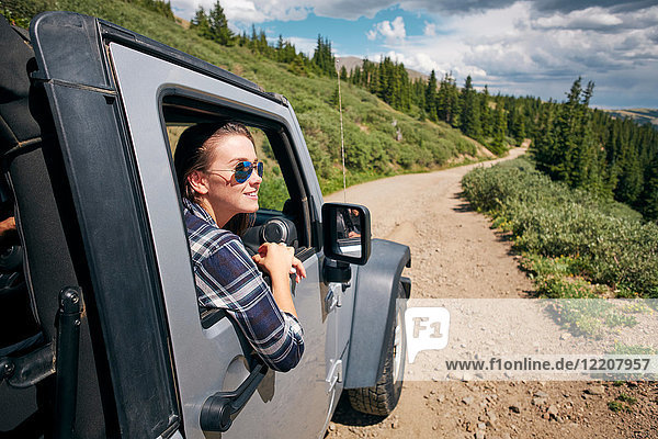 Junge Frau auf Autoreise mit Blick aus dem Autofenster in den Rocky Mountains  Breckenridge  Colorado  USA