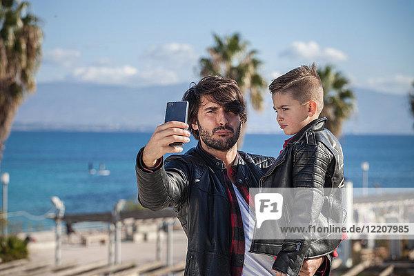 Vater und Sohn im Freien  Vater nimmt sich selbst mit Smartphone