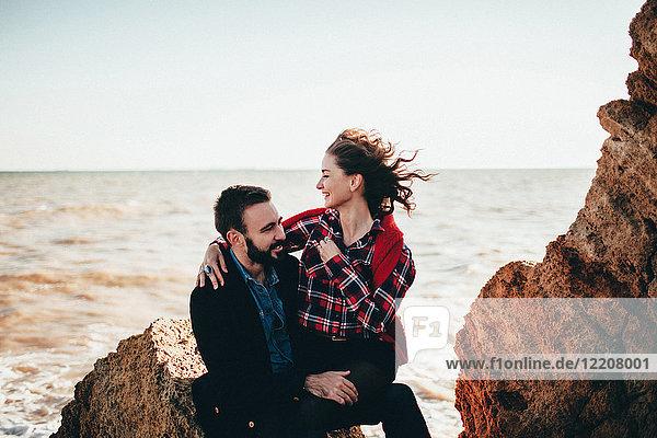 Romantisches Paar mittlerer Erwachsener auf Strandfelsen sitzend  Oblast Odessa  Ukraine