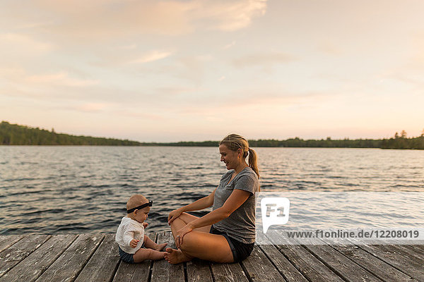 Mother sitting cross legged on lake pier with baby daughter