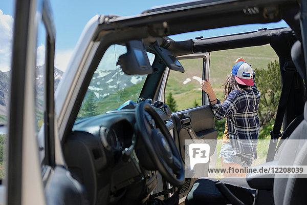 Junge Frau im Geländewagen mit Blick auf die Rocky Mountains  Breckenridge  Colorado  USA