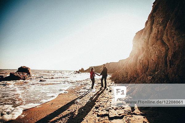 Mittelgroßes erwachsenes Paar  das am sonnenbeschienenen Strand Händchen hält  Oblast Odessa  Ukraine