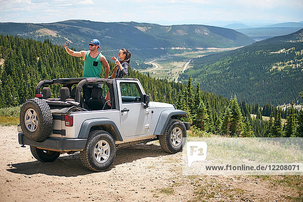 Road trip couple in parked four wheel convertible taking selfie in Rocky mountains  Breckenridge  Colorado  USA