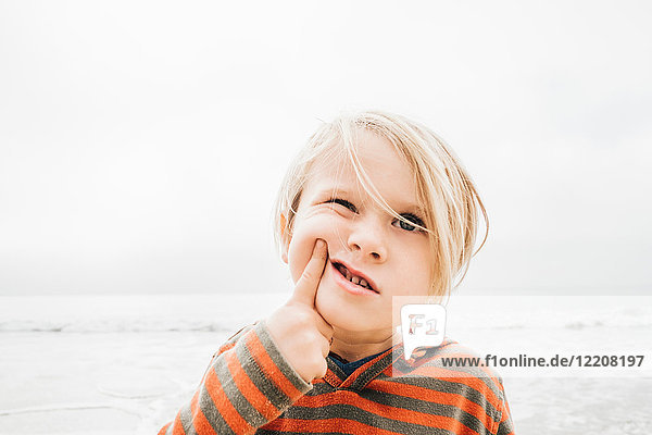 Portrait of young boy on beach  finger on face  making faces