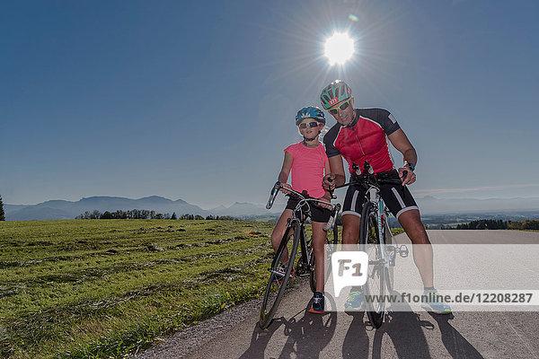 Porträt eines Mädchens und eines Radfahrervaters auf einer sonnenbeschienenen Landstraße