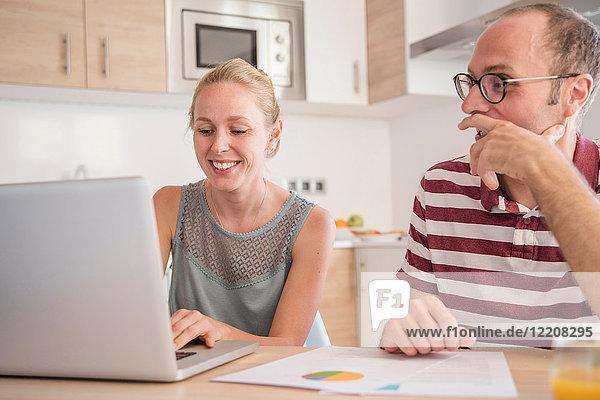 Junge Frau und Freund erledigen Papierkram und benutzen Laptop am Tisch