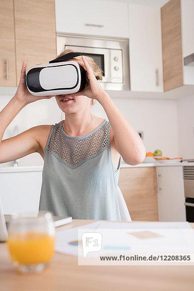 Junge Frau schaut durch ein Virtual-Reality-Headset am Küchentisch