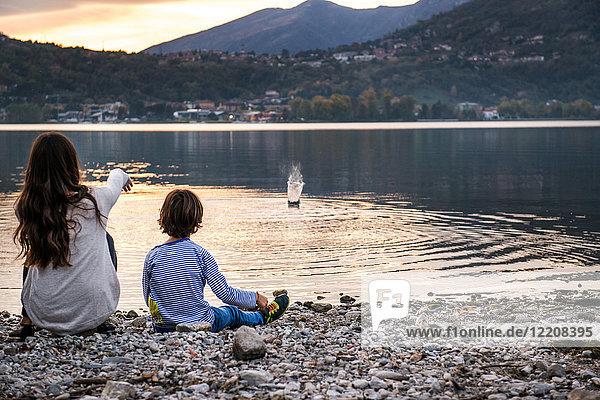 Rückansicht eines Jungen und einer jungen Frau  die in der Abenddämmerung Kieselsteine in den Fluss werfen  Vercurago  Lombardei  Italien