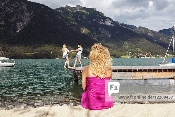 Woman watching couple on pier  Achensee  Innsbruck  Tirol  Austria  Europe