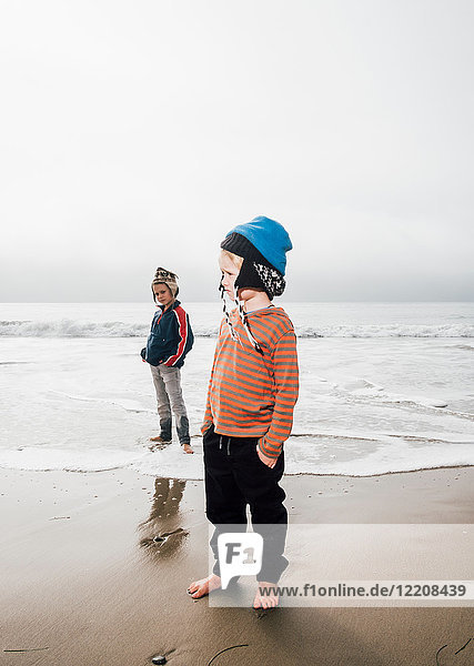 Portrait of two brothers  standing on beach  wearing knitted hats