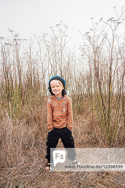 Portrait of boy in rural setting  hands in pockets  smiling