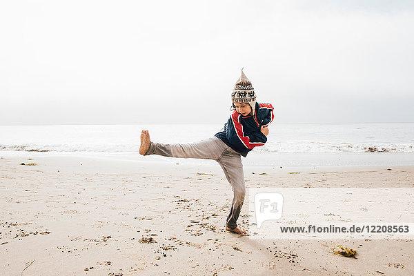 Young boy standing on beach balancing on one leg