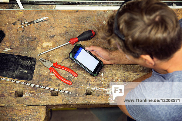 Man in workshop  using smartphone  overhead view