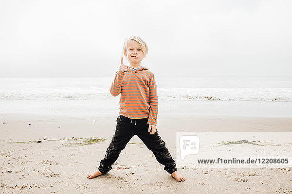 Portrait of young boy on beach  finger raised