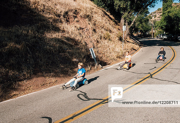 Three children  rolling downhill of toy cars