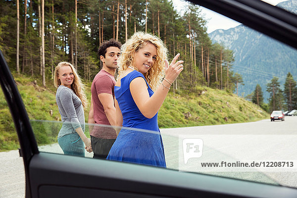 View through car window of friends looking over shoulder at camera  Innsbruck  Tirol  Austria  Europe