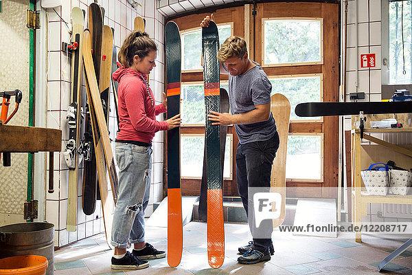 Mann und Frau in der Werkstatt  inspizieren Skiausrüstung