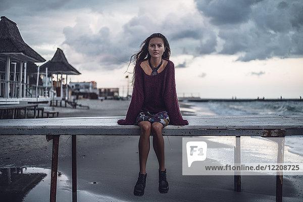 Porträt einer jungen Frau  die in der Abenddämmerung auf dem Pier sitzt  Oblast Odessa  Ukraine