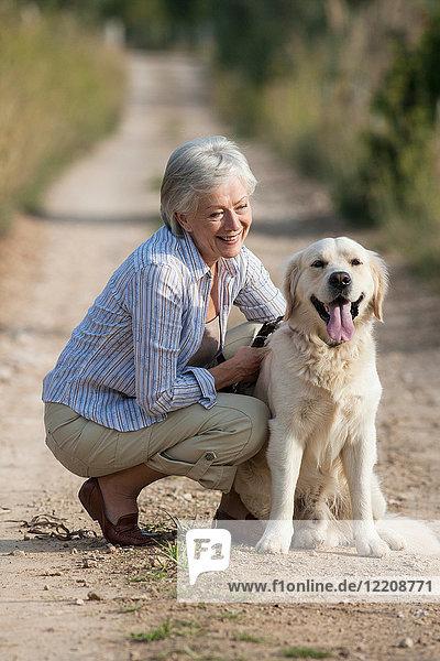 Portrait of senior woman crouching beside pet dog