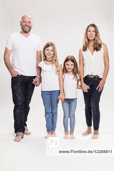 Studioporträt eines reifen Paares mit zwei Töchtern  in voller Länge