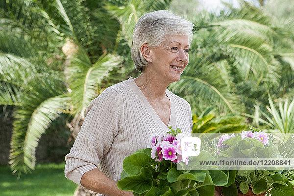 Ältere Frau im Garten  Pflanzen haltend