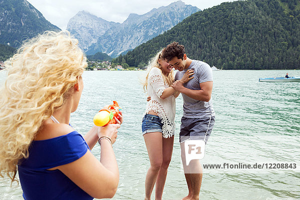 Woman squirting water pistol at friends  Innsbruck  Tirol  Austria  Europe