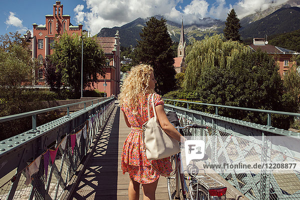 Rear view of woman with bicycle crossing footbridge  Innsbruck  Tirol  Austria  Europe
