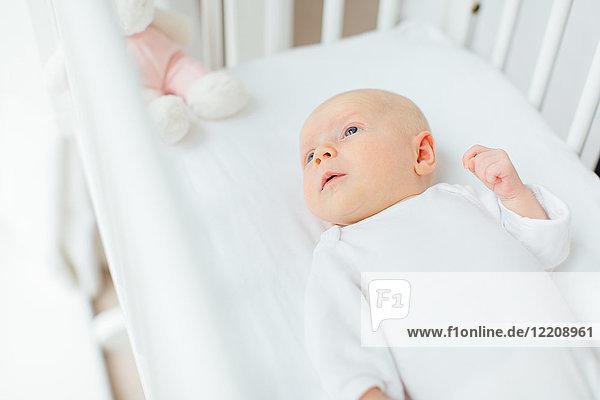 Draufsicht auf ein im Kinderbett liegendes Mädchen