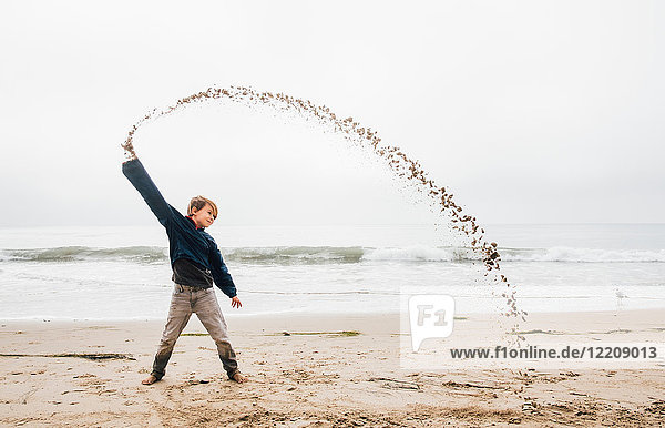 Portrait of young boy on beach  throwing sand in arch shape