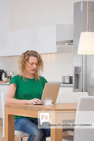 Woman sitting at kitchen table  using laptop