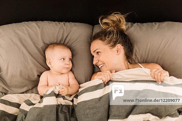 Im Bett unter der Bettdecke liegende Frau mit Baby-Tochter  Draufsicht