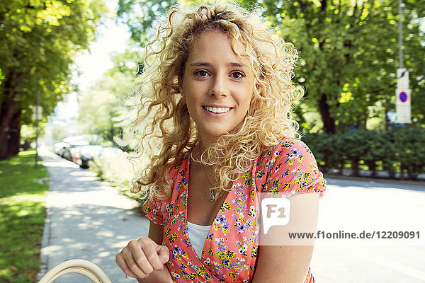 Portrait of curly haired blonde woman looking at camera smiling