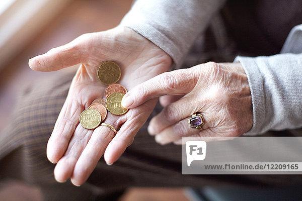 Ältere Frau zählt Münzen in der Hand  Nahaufnahme