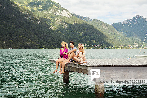Friends sitting together on edge of pier  Innsbruck  Tirol  Austria  Europe