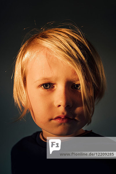 Portrait of boy with blonde hair  pensive expression