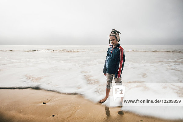 Portrait of boy standing on beach  pensive expression