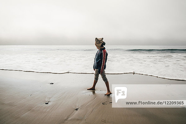 Young boy standing on beach  looking away