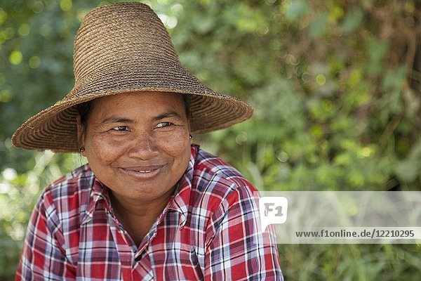 Local Burmese woman with straw hat on selling local crops in Myanmar.