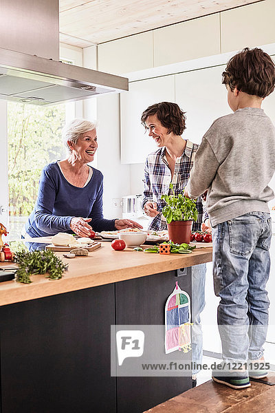 Young boy  mother and grandmother making pizza together in kitchen