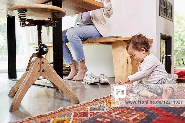 Mutter arbeitet am Küchentisch  während das Mädchen auf dem Boden spielt.