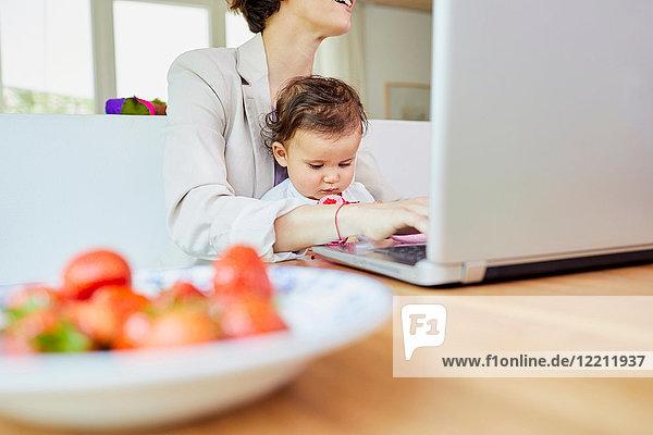 Mutter benutzt Laptop mit auf dem Schoß sitzendem Mädchen