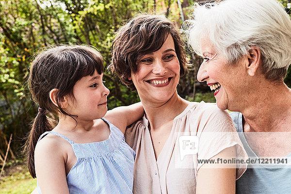 Porträt einer älteren Frau mit erwachsener Tochter und Enkelin  im Freien  lächelnd