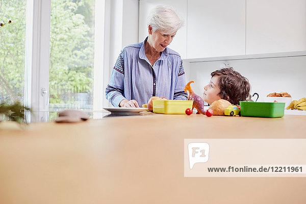 Großmutter und Enkel bereiten das Essen in der Küche zu