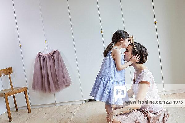 Mutter und Tochter im Schlafzimmer  von Angesicht zu Angesicht  Tochter küsst Mutter auf den Kopf