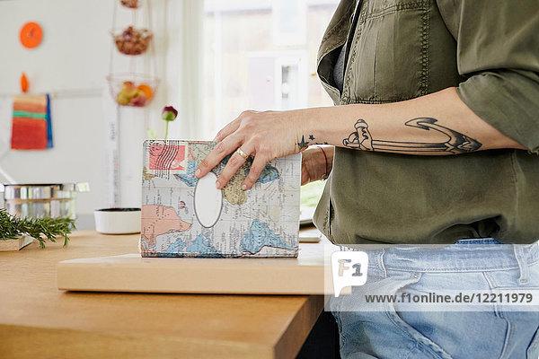 MId Erwachsener mit Tätowierungen auf dem Arm  Blick auf Buch in der Küche  Mittelteil