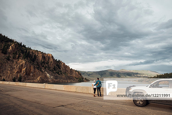 Couple standing on road beside Dillon Reservoir  looking at view  Silverthorne  Colorado  USA